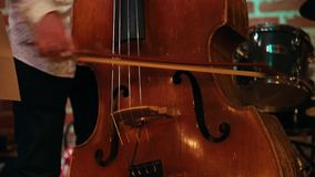 A man playing a double bass in a jazz bar, only his hands are visible. Close up stock video footage
