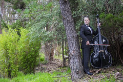 Man playing the double bass in park Royalty Free Stock Image