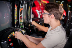 Man playing driving wheel video game. Young men playing driving wheel video game in game room Royalty Free Stock Images