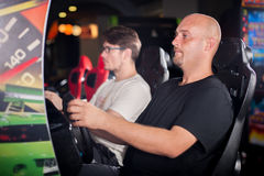 Man playing driving wheel video game. Young men playing driving wheel video game in game room Stock Photo