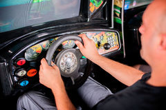 Man playing driving wheel video game. Young man playing driving wheel video game in game room Stock Photography