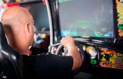 Man playing driving wheel video game. Young man playing driving wheel video game in game room Royalty Free Stock Photo