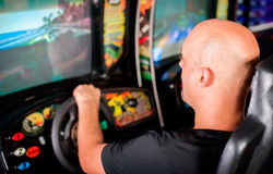 Man playing driving wheel video game. Young man playing driving wheel video game in game room Royalty Free Stock Photography