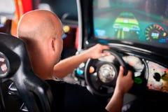 Man playing driving wheel video game. Young man playing driving wheel video game in game room Royalty Free Stock Image
