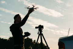 Man playing with drone, silhouette at sunset sky. Man playing with drone, silhouette against sunset sky. Young unrecognizable photographer running quadrocopter Stock Photography