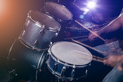 The man is playing drum set in low light background. Stock Image