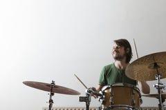Man Playing Drum Set. Smiling young men playing drum set Stock Photo