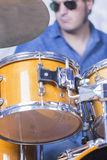 Man playing drums. Detail of a drum and a unfocused young male musician on the background is playing set of drums in a recording studio - focus on the top of the Royalty Free Stock Images