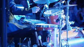 A man playing drums at the jazz concert with colorful lighting. Mid shot stock video