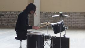 A man playing drums and preparing for the repetition. Mid shot