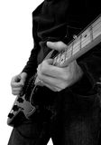 Man Playing Electric Guitar. Black and white image of man in jeans playing an electric rock guitar Royalty Free Stock Photos