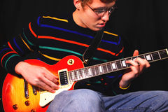 Man Playing Electric Guitar. A young man sitting and playing a classic, solid body,sunburst pattern electric guitar Stock Photos