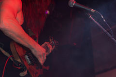 Man playing electric guitar at a j rock concert. Closeup of the instrument and hands of a man playing electric guitar live on stage at a jazz or rock concert in Royalty Free Stock Image