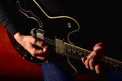 Man playing a electric guitar. Closeup, no face. stock photography