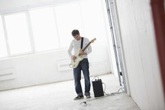 Man Playing Electric Guitar In Warehouse Stock Image