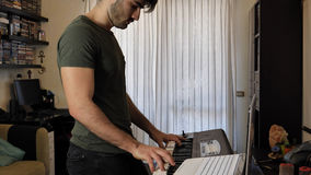 Man playing electric piano or electronic keyboard. Side view of male musician playing electric piano or electronic keyboard or synthesizer at home Stock Photography