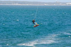 The man playing extreme action by jumping above the sea water with kitesurfing board in green color at Brighton le sands beach. A man playing extreme action by Stock Images
