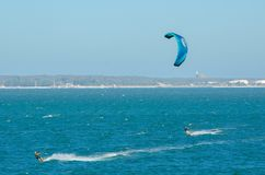 The man playing extreme action by jumping above the sea water with kitesurfing board in green color at Brighton le sands beach. A man playing extreme action by Royalty Free Stock Photo