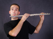 Man Playing Flute. A young man playing a metal flute which is a wind instrument Royalty Free Stock Photos