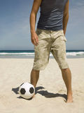 Man playing football on the beach. Royalty Free Stock Photos
