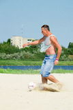 Man playing football on the sand Stock Images