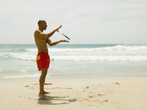 Man playing frisbee on the beach. Stock Photography