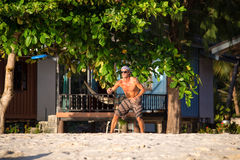 Man playing with frisbee on tropical beach in Koh Phangan, Thailand. Royalty Free Stock Photos