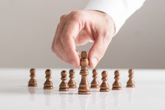 Man playing a game of chess on white table in a close up view Royalty Free Stock Image