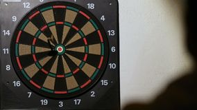 Man playing a game of darts, focus on target stock footage