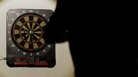 Man playing a game of darts, focus on target stock video