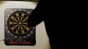 Man playing a game of darts, focus on target stock video footage