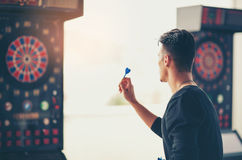 Man playing a game shooting darts Stock Photo