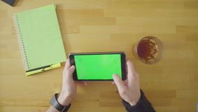 Man playing a game on tablet with green screen stock video footage