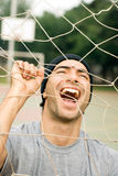 Man Playing With Goalie Soccer Net - vertical. A man holding onto a soccer goal net, smiling and yelling though it. - vertically framed Royalty Free Stock Image