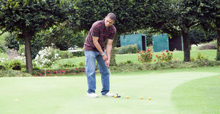 Man playing golf. Young man playing golf green field outdoors Stock Images