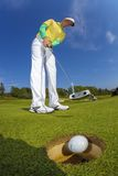 Man playing golf against blue sky Stock Photography