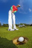 Man playing golf against blue sky Stock Photo