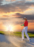 Man playing golf against colorful sunset. Man playing golf against sunset Royalty Free Stock Photos