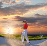 Man playing golf against colorful sunset. Man playing golf against sunset Royalty Free Stock Photo