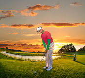 Man playing golf against colorful sunset Royalty Free Stock Photos