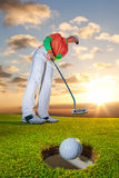 Man playing golf against colorful sunset Stock Image