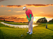 Man playing golf against colorful sunset Royalty Free Stock Image