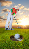 Man playing golf against colorful sunset Stock Photos