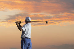 Man playing golf against sunset. After work Royalty Free Stock Photography
