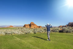 Man playing golf on a beautiful scenic desert golf course. Rear view of a man playing golf on a Sunny day on a beautiful desert golf course in the Southwestern Royalty Free Stock Photography