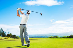 Man Playing Golf. On Beautiful Sunny Green Golf Course. Hitting Golf Ball down the Fairway from the Tee with Driver stock photo