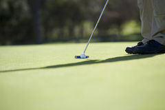 Man playing golf, close-up of feet and putter Stock Photo