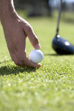 Man playing golf, close-up of hand, ball and tee Stock Images