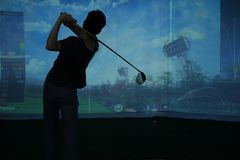 Man playing at golf course. Man playing golf at golf course on the 2013 asia golf show ,shenzhen convention & exhibition center,shenzhen city,china Royalty Free Stock Image