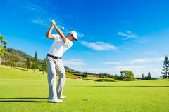 Man Playing Golf. Golfer Hitting Golf Shot with Club on the Course Stock Photo